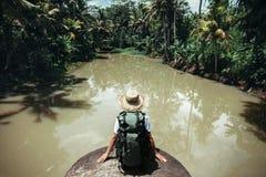 Jeune femme de voyageur s'asseyant avec le grand sac à dos et regardant la rivière tropicale Photographie stock