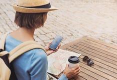 Jeune femme de voyageur s'asseyant dans une terrasse de caf? et un voyage de planification avec la carte et le smartphone voyage  image stock