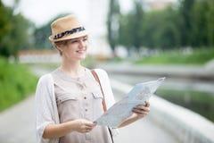 Jeune femme de voyageur vérifiant des vues sur la carte photographie stock libre de droits