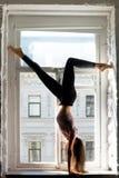 Jeune femme de yogi dans Adho Mukha Vrksasana, filon-couche de fenêtre photo libre de droits