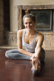Jeune femme de yogi dans la pose de Janu Sirsasana, backgroun d'intérieur de maison photos stock