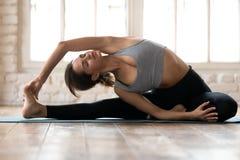 Jeune femme de yogi dans la pose de Parivrtta Janu Sirsasana image stock
