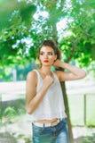 Jeune femme dehors dans un T-shirt blanc et des jeans, avec le maquillage lumineux, lèvres rouges Images stock