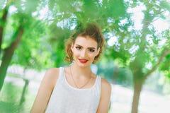 Jeune femme dehors dans un T-shirt blanc et des jeans, avec le maquillage lumineux, lèvres rouges Regarder l'appareil-photo Photographie stock libre de droits