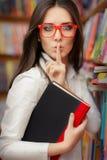 Jeune femme demandant le silence dans la bibliothèque Photographie stock