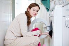 Jeune femme des travaux domestiques faisant la blanchisserie images stock
