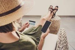 Jeune femme des vacances utilisant le téléphone et la carte de crédit Concept en ligne d'achats photos stock