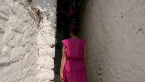 Jeune femme descendant une rue étroite entre les maisons blanches clips vidéos