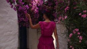 Jeune femme descendant une rue étroite entre les maisons blanches banque de vidéos