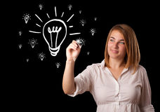 Femme dessinant l'ampoule sur le tableau blanc Image stock