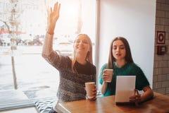 Jeune femme deux causant dans un café Deux amis appréciant le café ensemble Photographie stock libre de droits