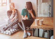 Jeune femme deux causant dans un café Deux amis appréciant le café ensemble Photographie stock