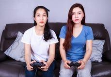 Jeune femme deux employant le contrôleur de manette jouant le jeu vidéo dessus Photos stock