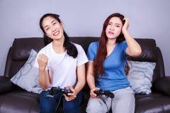 Jeune femme deux employant le contrôleur de manette jouant le jeu vidéo dessus Image stock