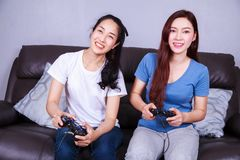 Jeune femme deux employant le contrôleur de manette jouant le jeu vidéo dessus Photographie stock libre de droits