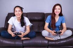 Jeune femme deux employant le contrôleur de manette jouant le jeu vidéo dessus Images stock