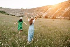 Jeune femme deux heureuse attirante marchant sur le champ avec des fleurs par la montagne sur le coucher du soleil Concept de Fre Photo stock