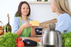 Jeune femme deux heureuse faisant la cuisson dans la cuisine Amitié et concept culinaire Photos stock