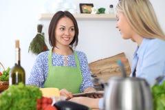 Jeune femme deux heureuse faisant la cuisson dans la cuisine Amitié et concept culinaire Photos libres de droits