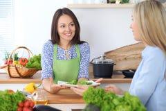 Jeune femme deux heureuse faisant la cuisson dans la cuisine Amitié et concept culinaire Photographie stock