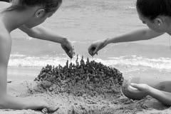 Jeune femme deux jouant avec le sable sur la plage Photographie stock libre de droits