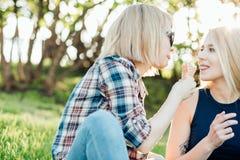 Jeune femme deux mangeant des cornets de crème glacée le jour chaud d'été pendant leurs vacances Photographie stock