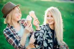 Jeune femme deux mangeant des cornets de crème glacée le jour chaud d'été pendant leurs vacances Images stock