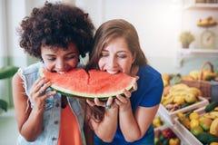 Jeune femme deux mangeant la pastèque et ayant l'amusement Photos libres de droits