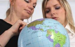 Jeune femme deux retenant un globe Images libres de droits
