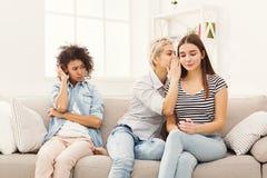 Jeune femme disant à son ami quelques secrets Image stock