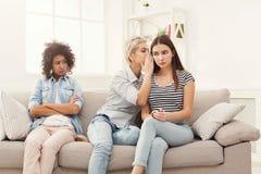 Jeune femme disant à son ami quelques secrets Photo stock