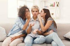 Jeune femme disant à son ami quelques secrets Photographie stock