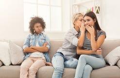 Jeune femme disant à son ami quelques secrets Images libres de droits