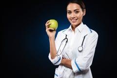 Jeune femme docteur de sourire tenant la pomme et regardant l'appareil-photo d'isolement Image libre de droits