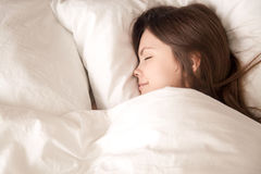 Jeune femme dormant bien sous la couverture chaude images stock