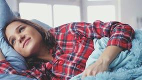 Jeune femme dormant dans le lit et se réveillant le matin et le sourire Photographie stock