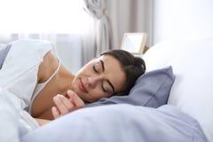 Jeune femme dormant sur l'oreiller mol photographie stock