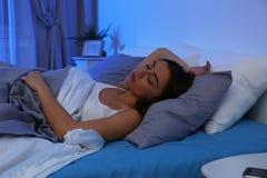 Jeune femme dormant sur l'oreiller mol la nuit photo stock