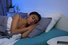 Jeune femme dormant sur l'oreiller mol la nuit photos libres de droits