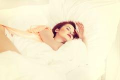 Jeune femme dormant sur la literie blanche dans le lit à la maison Images libres de droits
