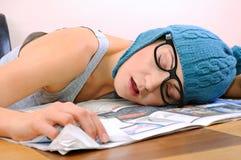 Jeune femme dormant sur la table Image stock