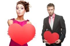 Jeune femme drôle et homme bel tenant le coeur rouge sur le Ba blanc Image libre de droits