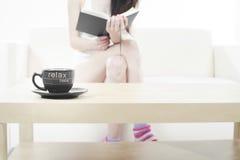 Jeune femme détendant dans un sofa et affichant un livre Photo stock
