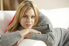 Jeune femme détendant à la maison Photo stock