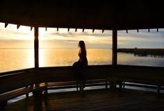 Jeune femme détendant sur le pilier sur le lac au coucher du soleil Image stock