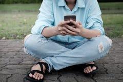 Jeune femme du hippie de la main à l'aide du téléphone intelligent sur la route de brique photographie stock