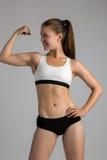 Jeune femme dure se tenant sur le fond gris Appareil-photo de regard femelle musculaire gants de port de bodybuilder prêts pour l Photographie stock libre de droits