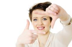 Jeune femme effectuant un geste de trame de photo Image libre de droits