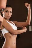 Jeune femme effrayée regardant son bras Image stock