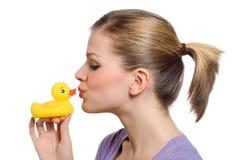Jeune femme embrassant le canard en caoutchouc jaune Images stock